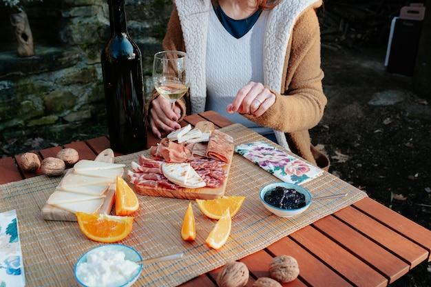 Mesa de piquenique com salsichas, queijos e comida tradicional italiana.