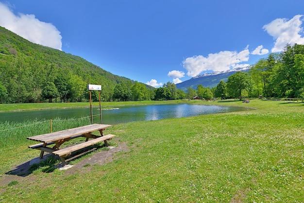 Mesa de piquenique de madeira na grama à beira de um lago em um parque de lazer nos alpes franceses