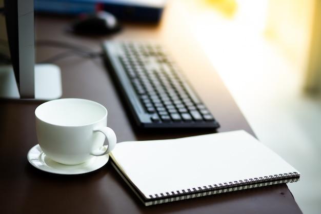 Mesa de proprietário de pme de negócios com computador de vidro notebook e copo branco café em casa negócio