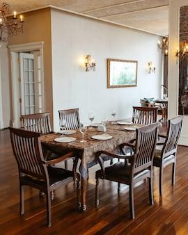 Mesa de restaurante com cadeiras de madeira, colocada no corredor, decorada em estilo clássico