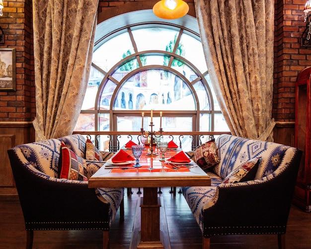 Mesa de restaurante com dois sofás perto da janela