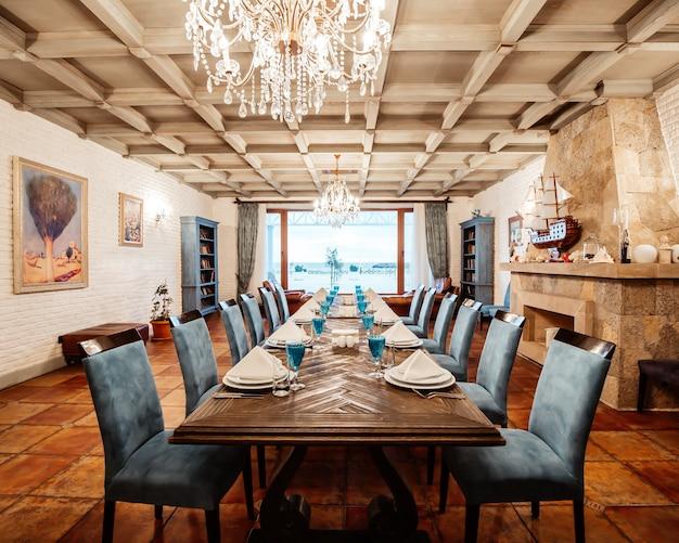Mesa de restaurante para 12 pessoas com cadeiras azuis, lareira, paredes de tijolos brancos e janela larga