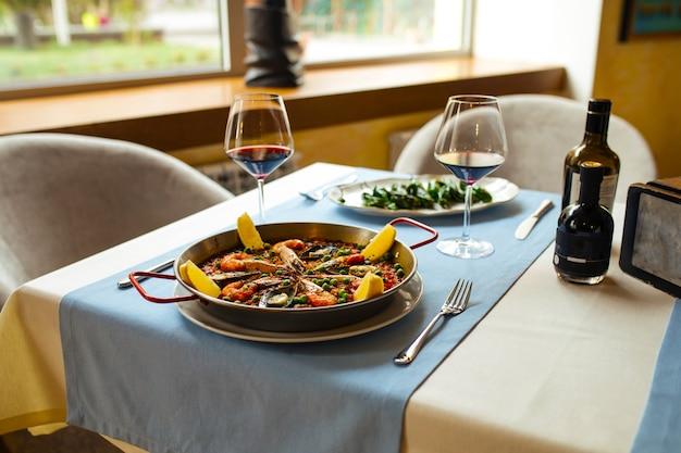 Mesa de restaurante servida com pratos espanhóis paella de frutos do mar e pimentos padronizados