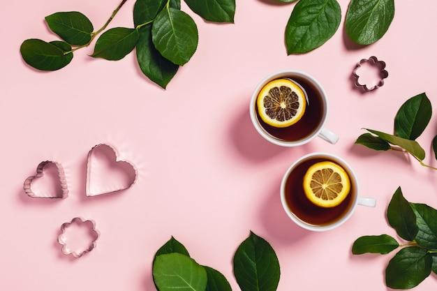 Mesa-de-rosa com duas xícaras de chá, cortadores de biscoito e folhas verdes.