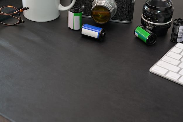 Mesa de secretária superior escura lerther do fotógrafo com câmera vintage, filmes, óculos, café e cópia espaço