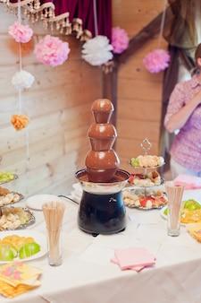 Mesa de sobremesa com fonte de chocolate e frutas