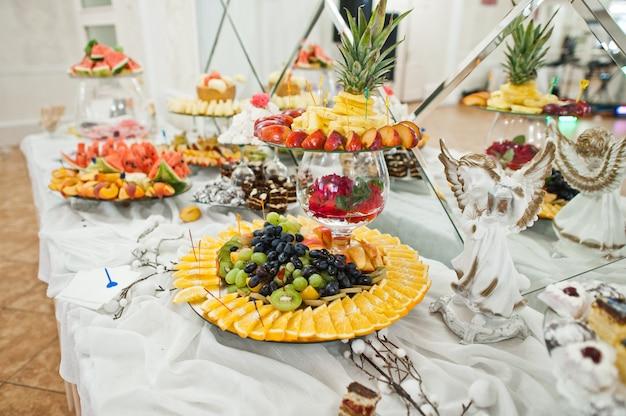 Mesa de sobremesa de deliciosas frutas na recepção do casamento.