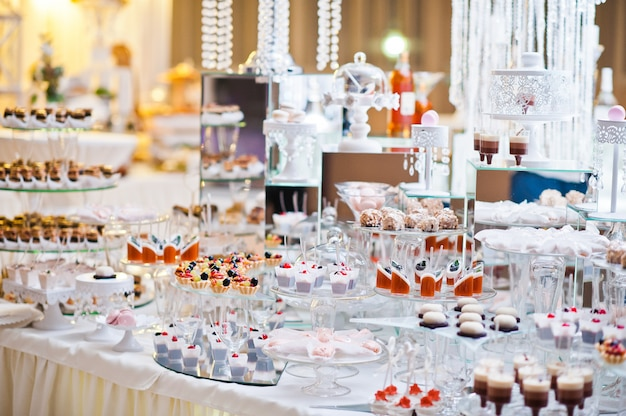 Mesa de sobremesa de deliciosos doces na recepção do casamento.