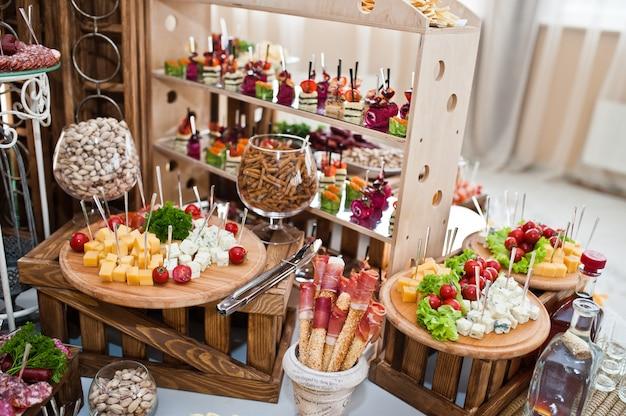 Mesa de sobremesa de deliciosos petiscos na recepção do casamento.