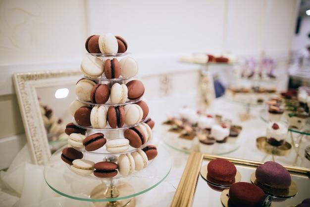 Mesa de sobremesa na recepção de casamento com macaroons vermelhos e brancos