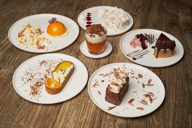 Mesa de sobremesas com bolinho, mousse, biscoitos, cheesecake. pedaço de bolo em um prato branco no fundo da mesa de madeira