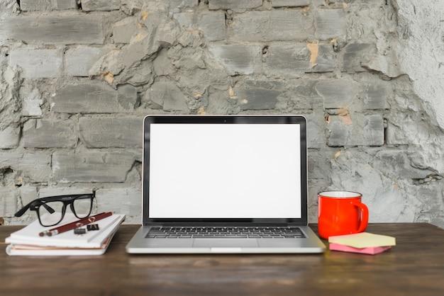 Mesa de trabalho arranjada com laptop; espetáculo; caneca de café vermelha e material de escritório