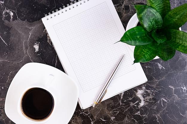 Mesa de trabalho com caderno, caneta, flor, em mármore.