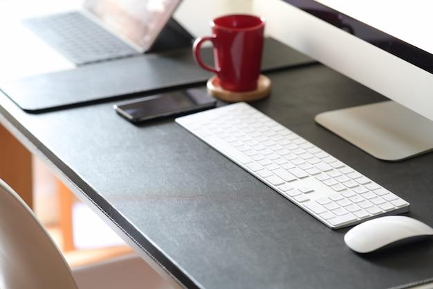 Mesa de trabalho com computador e material de escritório