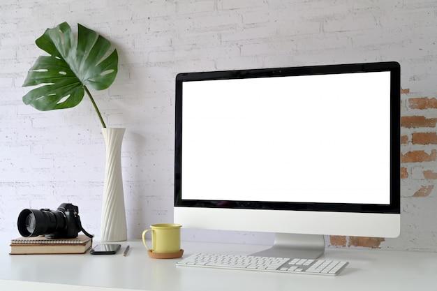 Mesa de trabalho com computador moderno e pôster de maquete