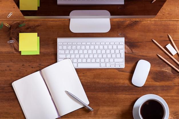 Mesa de trabalho com computador monitor teclado aberto notebook e café, plana leigos