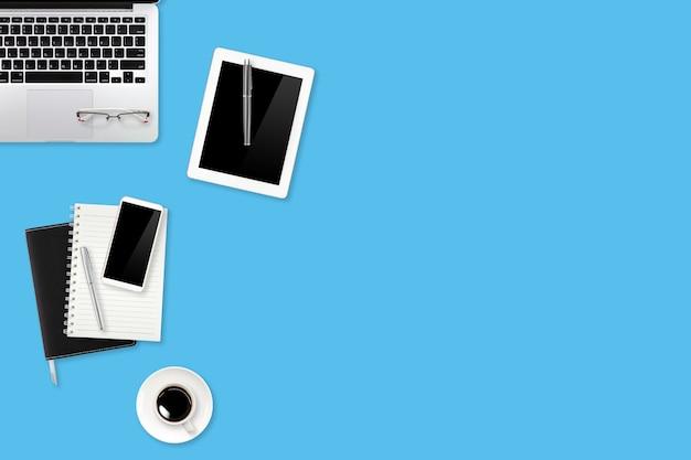 Mesa de trabalho com computador portátil, material de escritório, xícara de café, telefone celular e xícara de café sobre fundo azul pastel