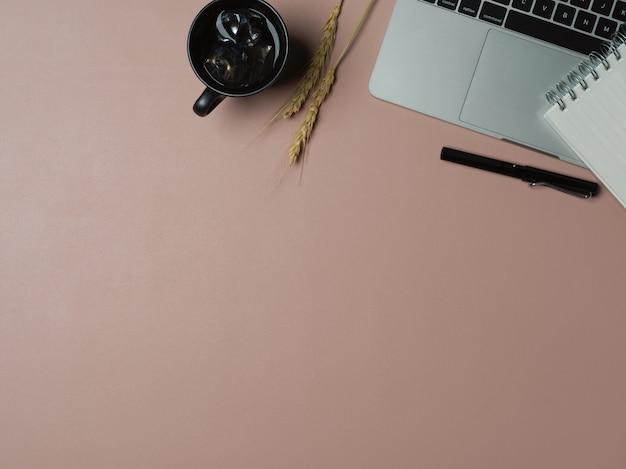 Mesa de trabalho com espaço de cópia, laptop, caneca de café e papelaria na mesa rosa