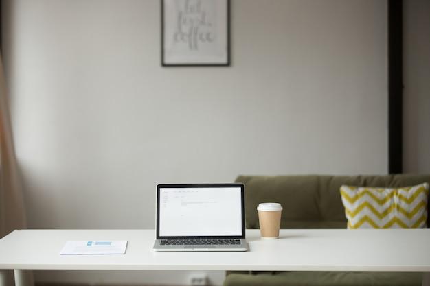 Mesa de trabalho com laptop, café e documentos no interior de casa