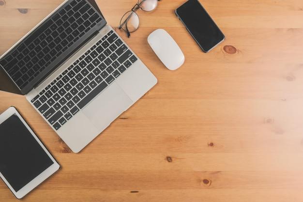 Mesa de trabalho com laptop, celular e tablet