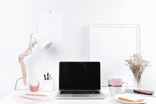 Mesa de trabalho com laptop e lanches