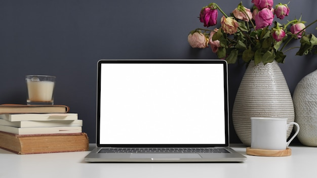 Mesa de trabalho com laptop, livros, xícara e vaso de flores no escritório em casa, traçado de recorte