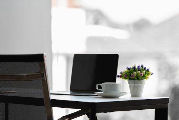 Mesa de trabalho com laptop, xícara de café, vaso de flores.