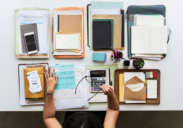 Mesa de trabalho com livros, papel e um par de óculos