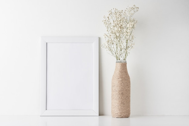 Mesa de trabalho com moldura vazia e flor em vaso