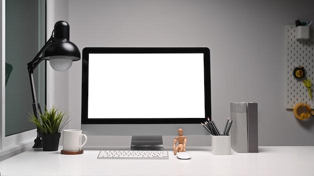 Mesa de trabalho confortável de designer ou artista com computador de tela em branco e várias ferramentas na mesa branca.