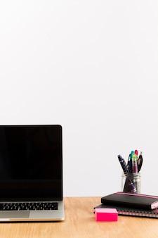 Mesa de trabalho contemporânea com laptop e bloco de notas no topo