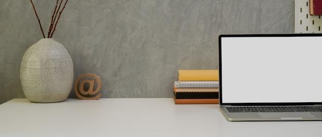 Mesa de trabalho de designer com espaço de cópia, laptop, papelaria, ferramentas de pintura, livros e xícara de café