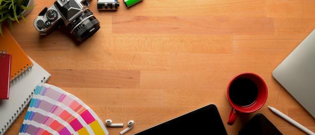 Mesa de trabalho de designer com espaço para cópia, câmera, dispositivos digitais e suprimentos de designer