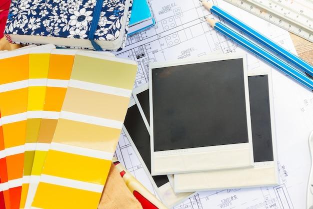 Mesa de trabalho de designers de interiores, planta arquitetônica da casa, guia de paleta de cores e amostras de tecido em tons amarelos, espaço de cópia em fotos vazias instantâneas