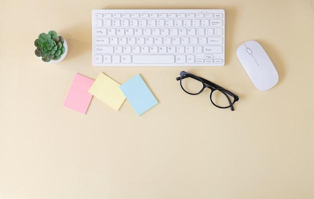 Mesa de trabalho de escritório com teclado de computador, mouse, óculos, adesivos em branco e vista superior da planta