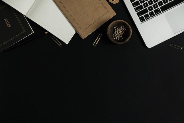 Mesa de trabalho de escritório de fundo preto com computador laptop, folha de caderno artesanal