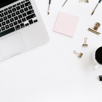 Mesa de trabalho de escritório em casa elegante rosa pálido com laptop, café e material de escritório na superfície branca