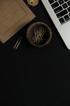 Mesa de trabalho de escritório preta com computador laptop, folha de caderno de ofício.