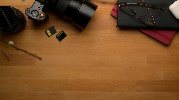 Mesa de trabalho de fotógrafo com espaço de cópia com câmera, óculos, livros de agenda e decoração