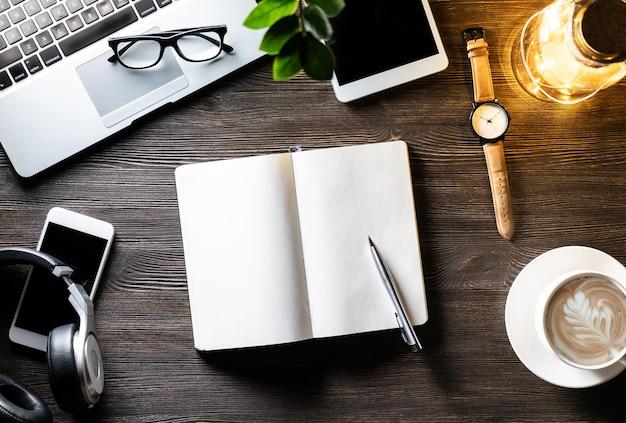 Mesa de trabalho de negócios com lâmpada luz no laptop telefone fones de ouvido digital tablet aberto caderno caneta óculos óculos assistir na mesa de madeira escura mesa de trabalho moderno com dispositivos, vista superior de cima