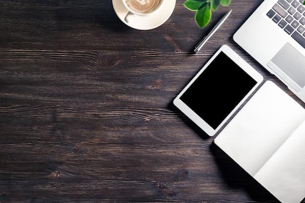 Mesa de trabalho de negócios com laptop e relógio de caneta digital tablet notebook na mesa de madeira escura, fundo de mesa moderno local de trabalho com dispositivos e xícara de café, vista superior de cima