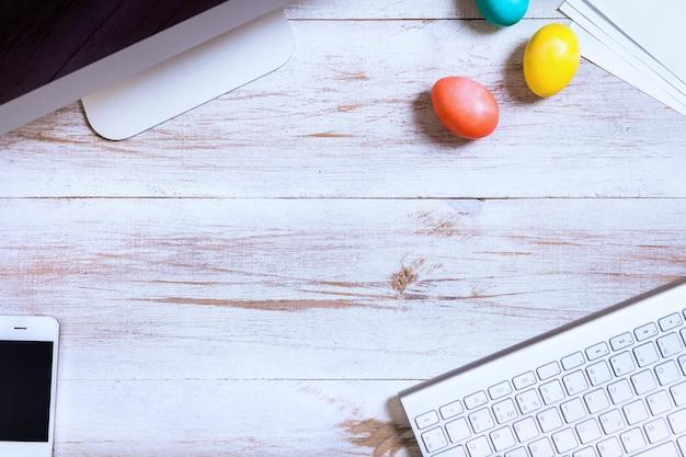 Mesa de trabalho de negócios e feliz páscoa fundo de ovos multicoloridos