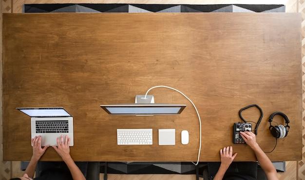 Mesa de trabalho de vista superior, mãos masculinas trabalhando no laptop na mesa de madeira, computador e mixer de som com espaço de cópia de fones de ouvido.