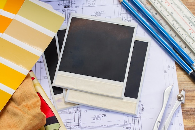 Mesa de trabalho do designer de interiores, planta arquitetônica da casa, paleta de cores e amostras de tecido em tons de amarelo, espaço de cópia em fotos vazias instantâneas