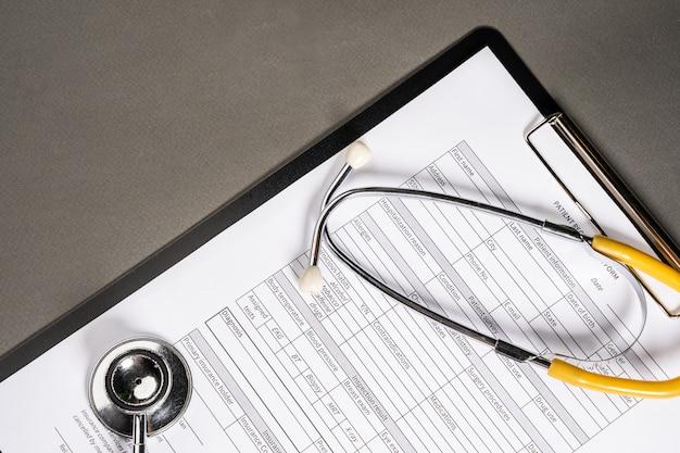 Mesa de trabalho do médico de medicina. perfil do paciente e estetoscópio em cima da mesa.