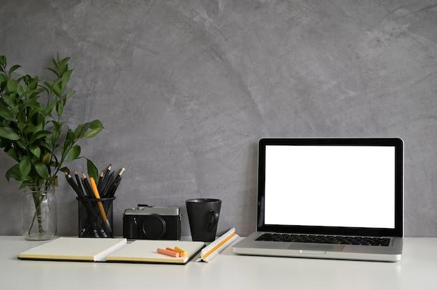 Mesa de trabalho e laptop, câmera, café na mesa criativa com parede do sotão.