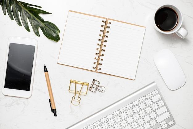 Mesa de trabalho elegante com páginas de caderno em branco, teclado, óculos, smartphone e caneca de café na mesa de mármore