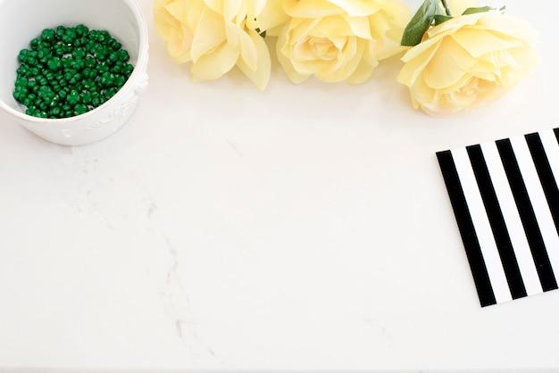 Mesa de trabalho elegante em mármore claro com rosas amarelas