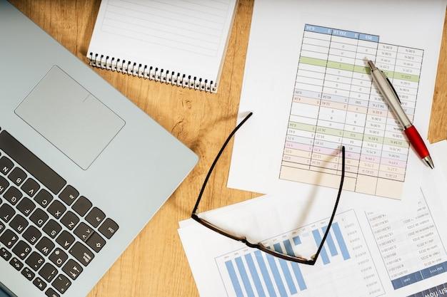Mesa de trabalho em casa com caneta, papéis, contas, gráficos, óculos, computador e calculadora. trabalho de conceito em casa, contas correntes, economia doméstica. vista aérea.