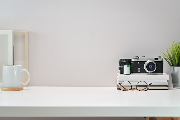 Mesa de trabalho escandinavo branco com câmera vintage, filmes, cartaz e cópia espaço